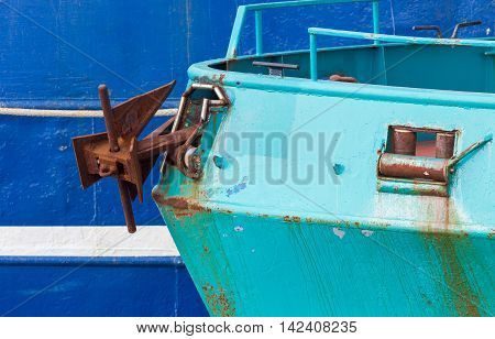 Nose of the green fishing ship larger blue ship in the background