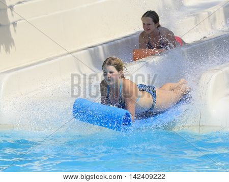 Rhodes Greece-August 12016: Two girl on the mat racer slide.Mat racer slide is very popular for young people in the Water Park. Water Park is located on the island of Rhodes in Greece and one of the most largest in Europe and is a very popular place
