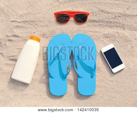 Summer Accessories Red Sunglasses And Flip Flops With Sunscreen Bottle Smartphone Lie On Sand Beach