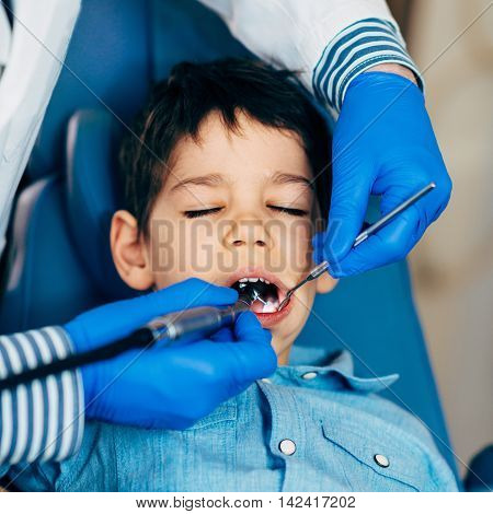 Dentist drilling little boy's tooth, square image
