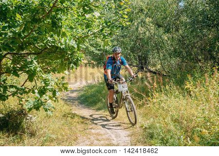 Gomel, Belarus - August 9, 2015: Cyclist Adult Man In Sports Equipment Riding On Mountain Bike On Winding Sandy Track Trail In Sunny Bright Greenwood. Healthy Lifestyle Concept.