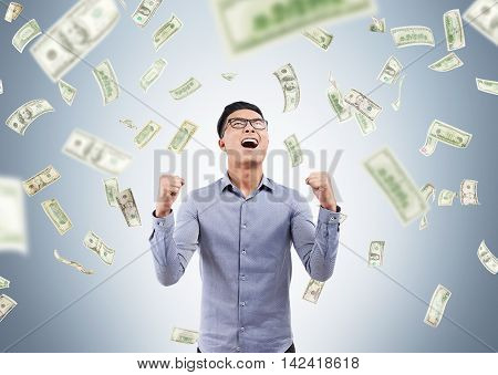 Excited Asian man standing with arm folded in money rain and screaming with joy. Concept of sudden enrichment