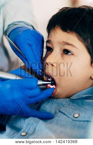 Dentist drilling little boy's tooth, vertical image