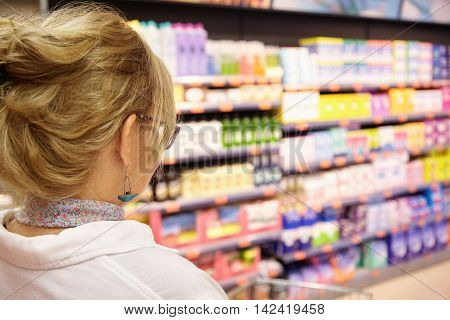Back Shot Of Grandmother With Blonde Hair Shopping At Local Supermarket, Pushing Cart Forward Going