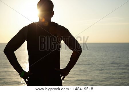 Silhouette Of Young Dark-skinned Athlete Relaxing After Running Workout At Seaside, Standing On Coas