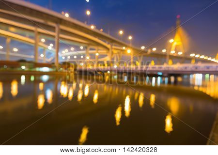 Blurred bokeh lights highway and suspension bridge with reflection