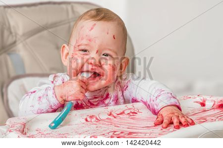 Messy And Dirty Baby Is Eating From Spoon.