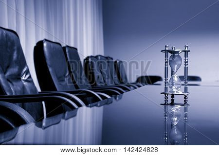 Empty conference room business meeting concept blue toned sand clock in the empty conference room