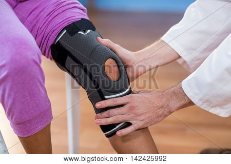 Physiotherapist examining female patients knee in the clinic