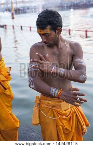 Ujjain Madhya Pradesh India - May 18 2016: A young priest paints his arm before a fire ceremony called 'aarti' at the Kshipra River during the Kumbh Mela religious festival in Ujjain India on May 18 2016. Kumbh Mela is the largest gathering on Earth which