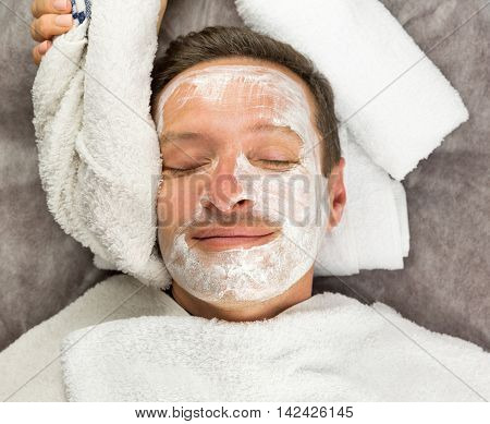 Macro view of smiling face of man with cream mask towels beauty spa