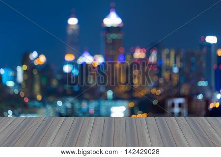 Opening wooden floor, blurred lights night view city office building, abstract background