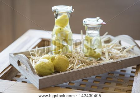 Jugs of lemon water and lemons on an wooden tray