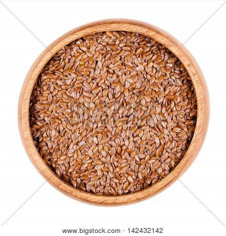 Brown flaxseeds in a wooden bowl on white background. Also known as common flax or linseed. Raw edible food. Linum usitatissimum of the Linaceae family. Isolated, macro photo and close up from above.