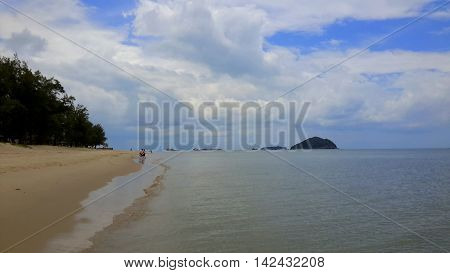 billowing cumulus clouds above a flat sea, a few distant people on the beach, two islands and several ships on the horizon, wet sand left from receding waves, Songkhla, Thailand
