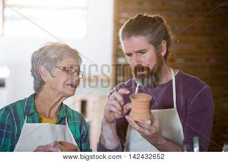 Male potter assisting female potter for making pot in pottery workshop