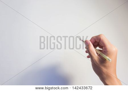 take pencil in the hand with white wall