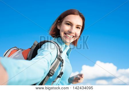 happy woman mountain hiker go to travel and take a selfie with blue sky and white clouds caucasian