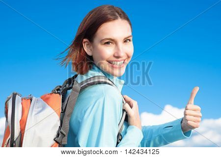 happy woman mountain hiker show thumb up and take a selfie with blue sky and white clouds caucasian