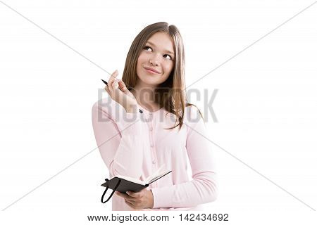 Girl in pink cardigan is standing and holding her notebook and pen dreaming about bright future. Concept of dream big and it will come true. Isolated
