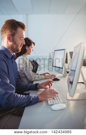 Mature student using computer in the computer room at college