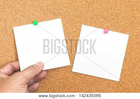 Blank white paper note with green pin on corkboard with hand holding