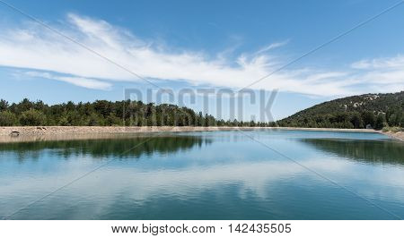 Water reservoir dam with forerst tree reflections at Prodromos village in Troodos mountains in Cyprus.