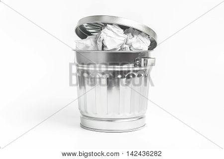 Stainless waste basket filled with crumpled paper on white background waste or frustration concept