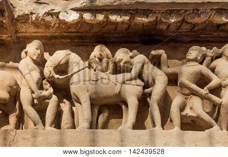 Intimate life of ancient people on stone relief on wall of Khajuraho temple India. UNESCO Heritage site built between 950 and 1150 in India belong to Hinduism and Jainism.