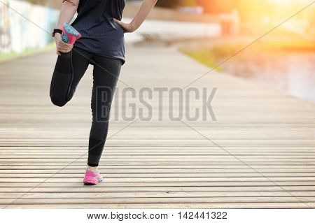 Woman stretching legs before workout and exercise. Marathon
