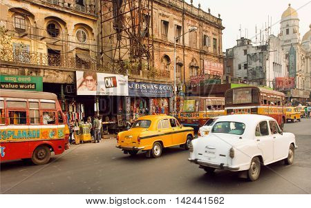KOLKATA, INDIA - JAN 14, 2016: Traffic on indian road with markets and speeding antique Ambassador cars on January 14, 2016. First Ambassador was produced by the Yellow Cab Manufacturing Company in 1921