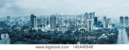 Aerial panoramic view of Jakarta, capital of Indonesia. Panorama of Jakarta skyscrapers at cloudy day, blue colored