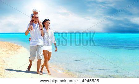Vista de la familia joven feliz divirtiéndose en la playa