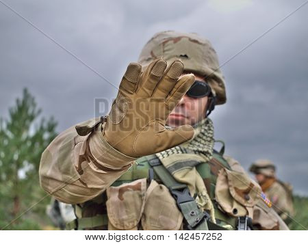 US Army soldier raises his hand in order to stop you do something