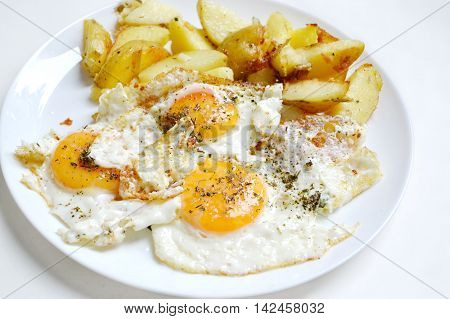 Big round plate full of fried eggs, french fries and cherry tomatoes - a traditional continental breakfast