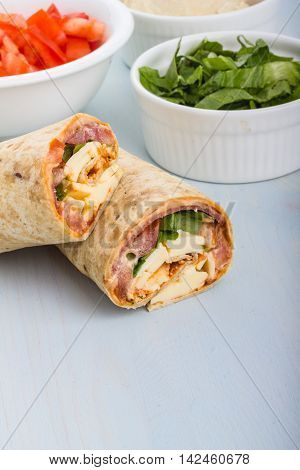 Pepperoni tomato lettuce harissa and hoummous gently wraped in tortilla.