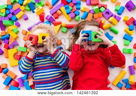 Happy preschool age children play with colorful plastic toy blocks. Creative kindergarten kids build a block tower. Educational toys for toddler or baby. Top view from above.