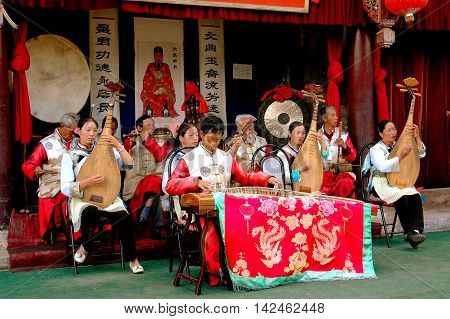 Lijiang China - April 19 2006: An orchestral ensemble of musicians in traditional Naxi people clothing giving a concert at the historic House of Mu