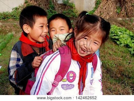 Lian Village China - November 26 2007: Three adorable Chinese children with happy smiles on their way home from school