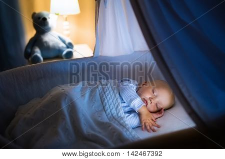 Adorable baby sleeping in blue bassinet with canopy at night. Little boy in pajamas taking a nap in dark room with crib lamp and toy bear. Bed time for kids. Bedroom and nursery interior. poster