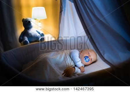 Adorable baby with pacifier sleeping in blue bassinet with canopy at night. Little boy in pajamas taking a nap in dark room with crib lamp and toy bear. Bed time for kids. Bedroom and nursery interior. poster