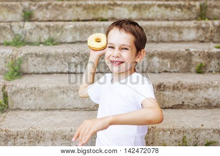 unny boy playing in the fight donuts. laughing child is going to throw a donut in his opponent. the concept of a fun party, irrational use of food, rejection of unhealthy and high-calorie sweets and pastries