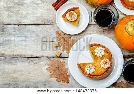 wooden background with pumpkin pies pumpkin and coffee. Autumn concept.