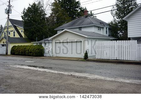 ROARING BROOK, MICHIGAN / UNITED STATES - DECEMBER 23, 2015: The garage of an elegant home behind a white picket fence on Pennsylvania Avenue in Roaring Brook.