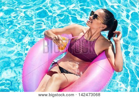 My environment. Positive content smiling beautiful woman sitting in the inflatable ring and drinking cocktail while swimming in a pool