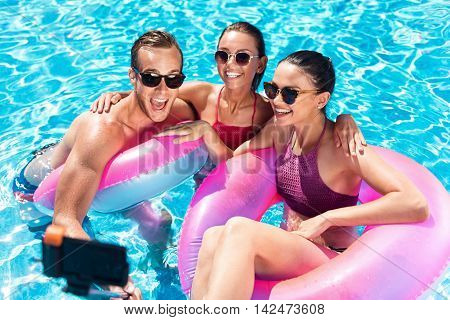 Enjoy your life. Cheerful content smiling friends sitting in a swimming pool and resting while making selfies