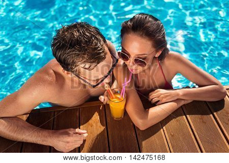 Fresh breath. Cheerful loving couple standing in the swimming pool and drinking cocktail while resting together