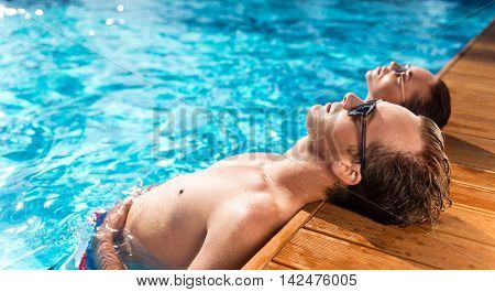 Find harmony with mind. Positive relaxed couple resting while enjoying time in the swimming pool