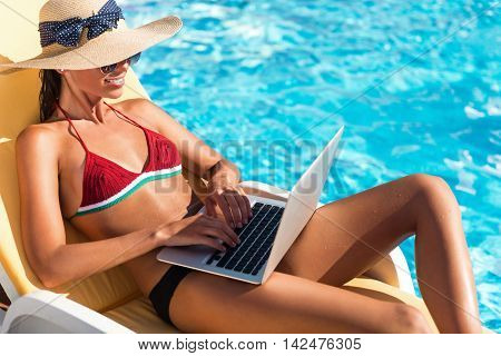 Break for work. Pleasant delighted beautiful woman sitting in the sun bed and using laptop while resting near swimming pool