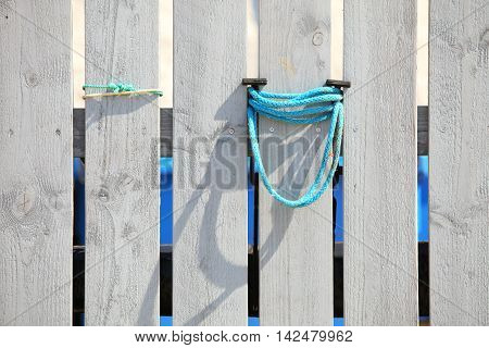 port detail wooden planks wall with blue rope as background